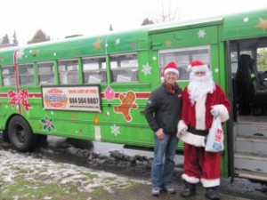 Jeff Leung and Santa in front of a Vancouver Christmas Bus